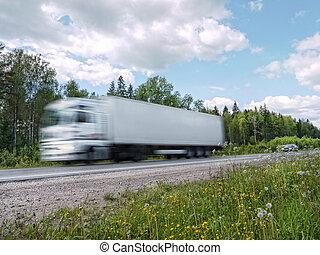 white truck speeding on rural highway, motion blur