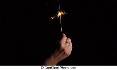 Burning sparklers in hand