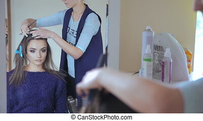 Young woman getting her hairdo in salon