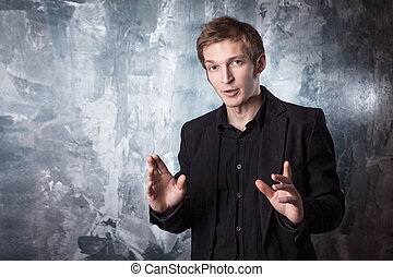 young man conducts a dialogue in black suit on textured grey...