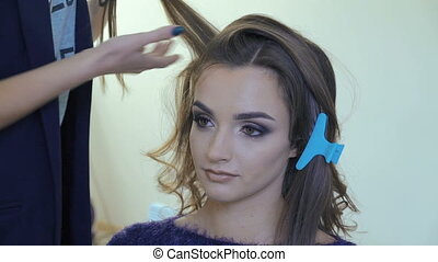 Professional hairdresser doing hairstyle for beautiful woman...