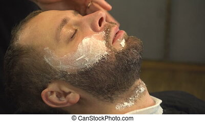 Barberman using soft cream on face of man with beard in...