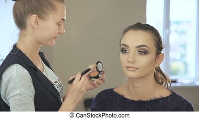 Makeup artist apply makeup to an attractive woman in full HD