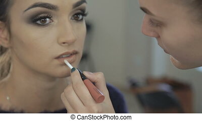 Close up of make up artist applying lipstick pencil on lips...