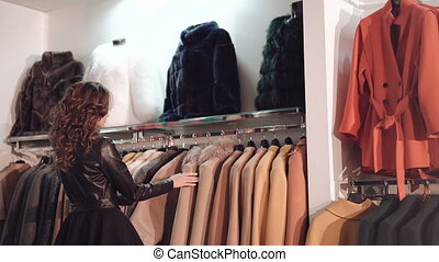 Fashionable lady choosing the rich coats in boutique in full...