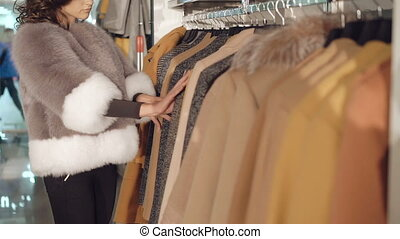 Fashionable lady choosing the fur coats in boutique in full...