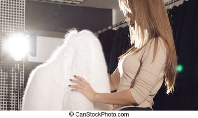 Pretty girl trying on the rich white fur coat in boutique in...