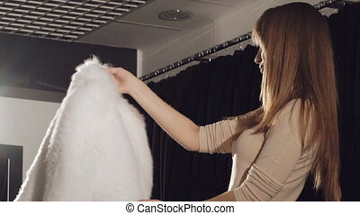 Smart girl trying on the rich white fur coat in boutique