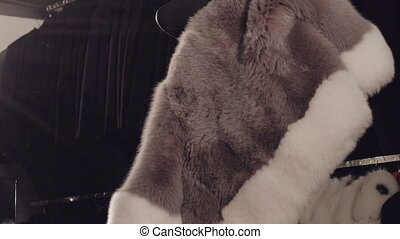 Smart girl trying on the rich fur coat and posing on camera in boutique