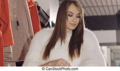 Enjoyable model posing in rich fur coat in boutique for...