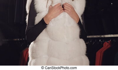 Happy woman posing in rich fur coat in boutique for camera