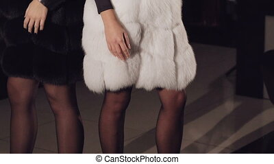 Glamour girls in fur coats flirting and posing in boutique...