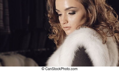 Happy girl posing in rich fur coat in boutique for camera in...