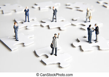Putting the pieces together - Businessman figurines placed...