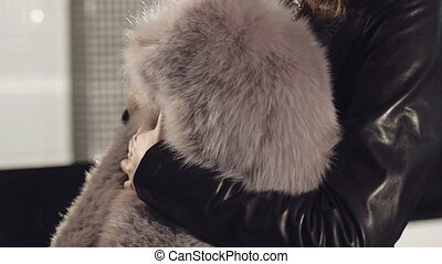 Smart girl trying on the rich fur coat in boutique