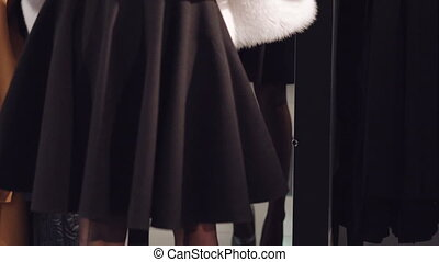 Smart girl trying on the rich fur coat to the mirror in...