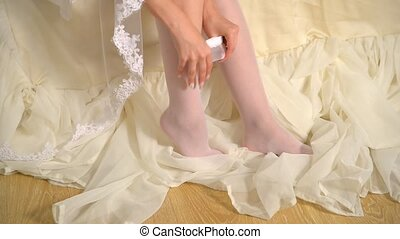 Putting stockings on sexy legs. Bride puts on garter on the...