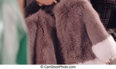 Happy woman trying on the rich fur coat to the mirror in...