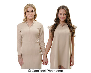 Two girls in beige dresses holding hands in studio - Young...