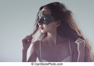 cute young girl with long flowing hair in masquerade mask