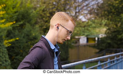 Young man with ginger hair listens to music in a park and texts, close up