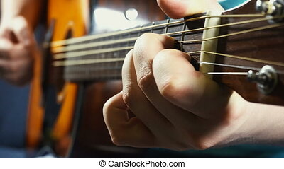 Man playing on acoustic guitar - Man guitarist playing on...
