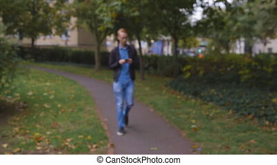 Young man with ginger hair walks up to the camera looking for directions on his phone
