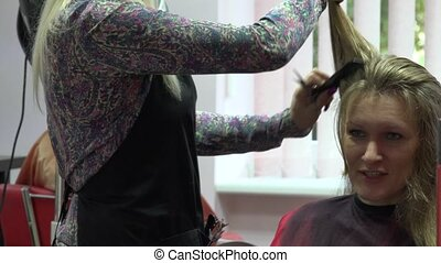 Happy blond woman talk with her personal hair stylist while making haircut. 4K