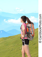 Woman climbing the moutain - Woman carrying a sports...