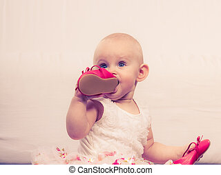 Baby girl biting shoe - Infant in time of teething. Sweet...