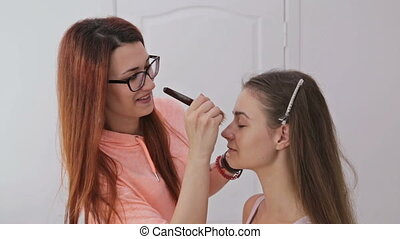 3 shots. Makeup artist applying liquid tonal foundation on...