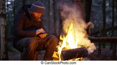 Man using compass and smart phone by campfire in the woods -...