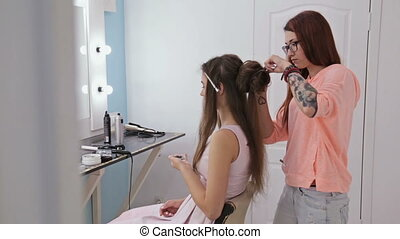 Professional hairdresser doing hairstyle for pretty woman...