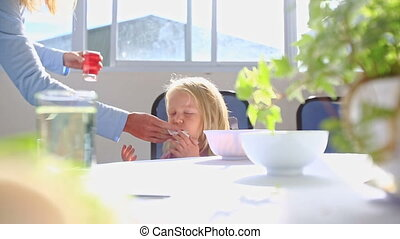 Little Blond Girl Sits at Table Mother Cleans Mouth Gives Juice