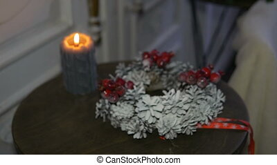 Christmas wreath and burning candle on the table. Soon holiday
