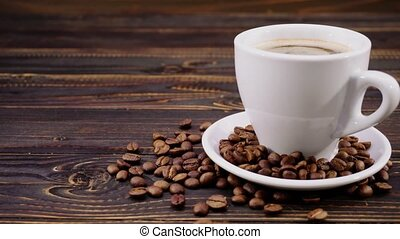 cup of coffee and roasted beans on wooden background - cup...