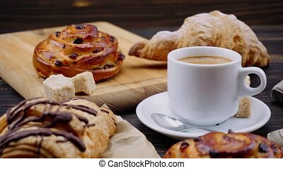 cup of coffee and croissants on wooden background - cup of...