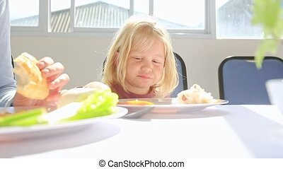 Little Blond Girl Eats Breakfast from Large Plate at Table -...
