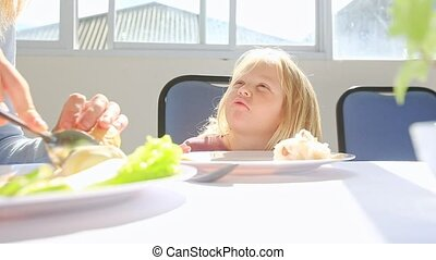 Little Blond Angry Girl Waits for Food from Mother at Table...