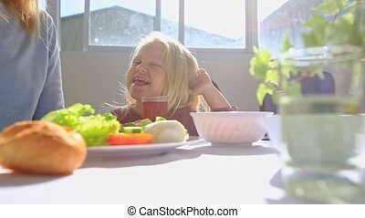 Little Blond Girl Sits at Table Drinks Juice Gambols Smiles