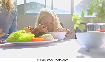 Little Blond Girl Eats with Spoon from Large Bowl at Table
