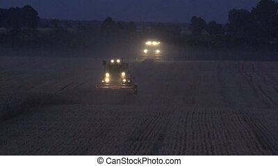 combine with lights thresh wheat field in farm in evening. 4K
