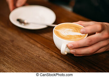 Man hands holding a cap of coffee.