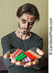 Drugs addict is holding tablets in both his hands - Drugs...