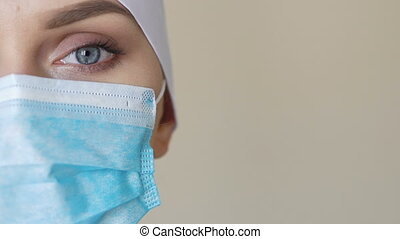 Female medical worker wearing face mask looking into camera....