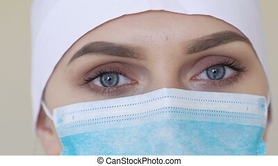 Female medical worker wearing face mask looking into camera...