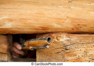 hunting rifle on a background of wooden house