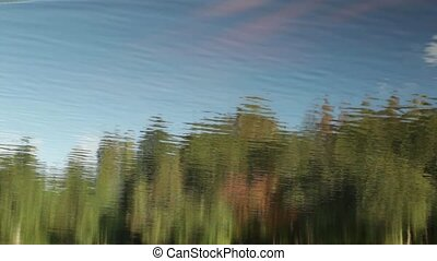 forest and blue sky reflection in the river abstract...