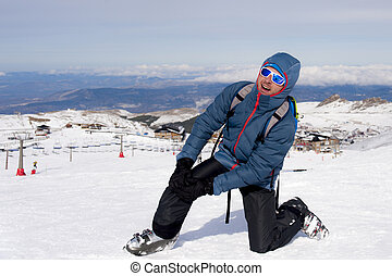 man lying on cold snow after ski crash holding his injured knee in pain at Sierrna Nevada resort