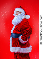 Portrait of a fairytale Santa Claus turned sideways over red...